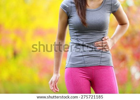 Side cramps - woman runner side stitch after running. Jogging woman with stomach side pain after jogging work out. Female athlete in colorful late summer autumn forest. - stock photo
