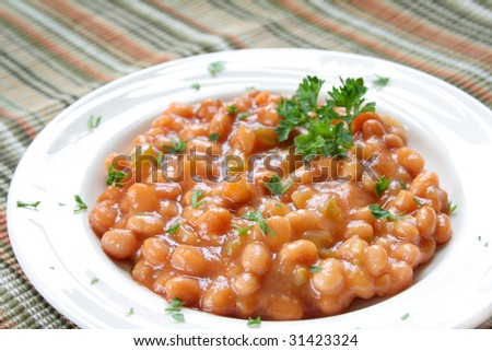Side dish of baked beans garnished with fresh parsley. - stock photo