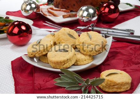 Side dish sage biscuits and carved roasted spiced ham appetizers with Christmas ornaments.  - stock photo