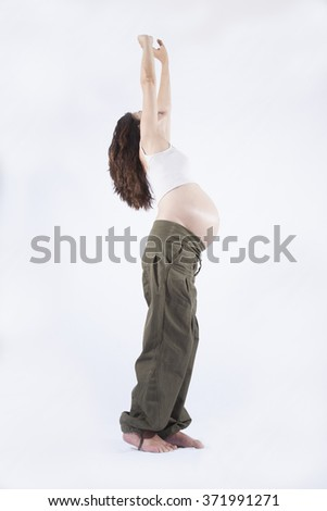 side eight month brunette pregnant woman naked paunch standing stretching arms up isolated over white background - stock photo