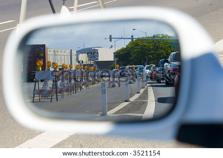 side mirror view of traffic and traffic cones blocking a street lane - stock photo