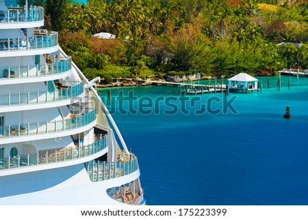 Side of a cruise ship with trees and ocean in background - stock photo