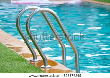 Side of a swimming pool with chrome stairs