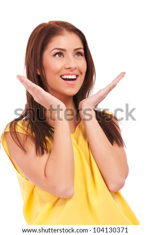 side of an excited young casual woman looking at something on white background