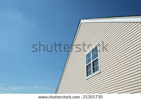 Side of new house showing peaked roof and blue sky. Pair of double-hung windows. - stock photo