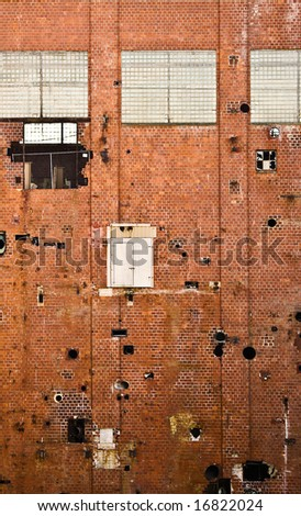 Side of old red brick building in factory demolition site. The building is full of holes, broken windows and an odd door several stories up with no stairs.