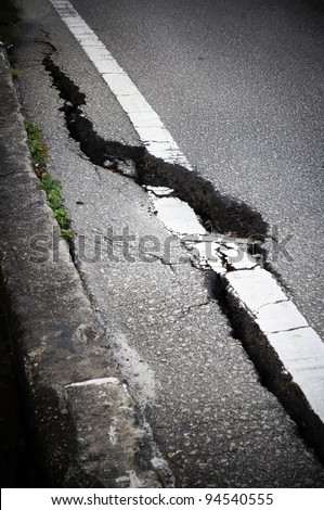 Side of the road cracking open slowly - stock photo