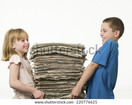 Side on studio portrait of two children carrying a large pile of newspapers against a white background - stock photo