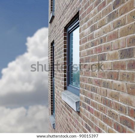 Side perspective of a glass window on a rustic brick wall against a cloudy blue sky. - stock photo