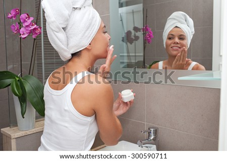 Side portrait and face reflection of a joyful young woman applying nourishing cream on her face, looking at herself in a bathroom mirror, with towel wrapping her hair, home interior. Skin care. - stock photo