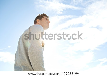 Side portrait low angle view of a man standing and looking ahead against a blue sky with sun rays filtering through his chest. - stock photo