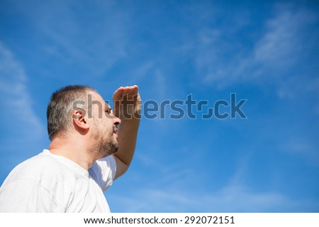 Side portrait low angle view of a man with beard standing and looking ahead against a blue sky with white clouds holding his hand up - stock photo