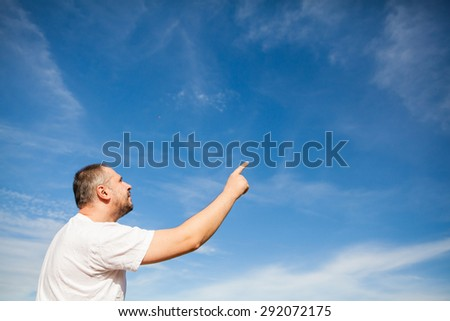 Side portrait low angle view of a man with beard standing and looking ahead against a blue sky with white clouds and pointing with finger - stock photo