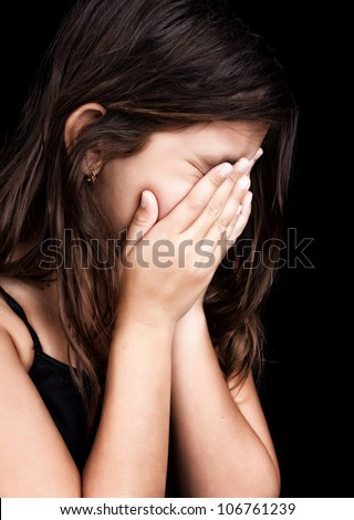 Side portrait of a beautiful girl crying and covering her face isolated on black - stock photo