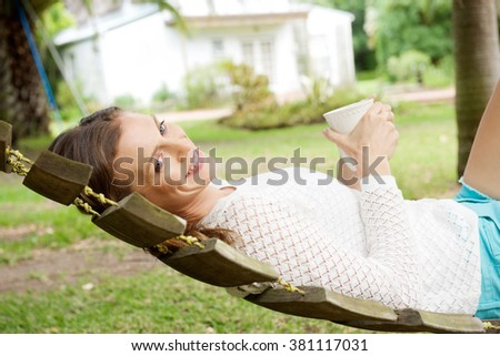 Side portrait of a beautiful woman relaxing on hammock with coffee cup - stock photo