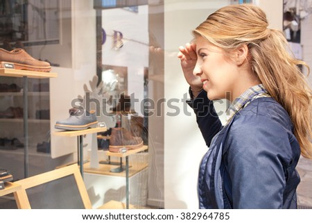 Side portrait of a blond caucasian teenager girl in a shopping street looking at shoe store window, smiling outdoors. Adolescent tourist consumer lifestyle. Young woman shopping recreation. - stock photo