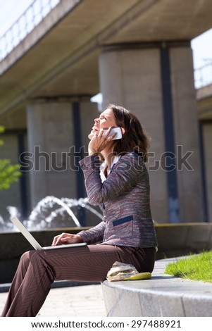 Side portrait of a business woman laughing with mobile phone and laptop in city park during lunch break - stock photo