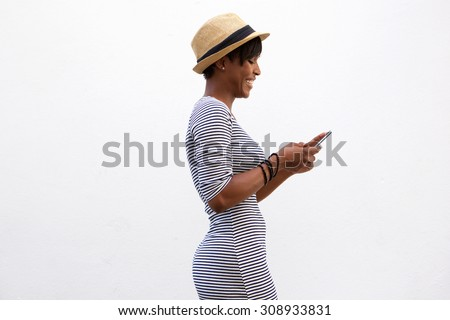 Side portrait of a cheerful young woman walking and texting - stock photo
