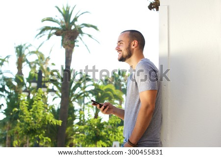Side portrait of a handsome young man holding mobile phone outside in summer - stock photo