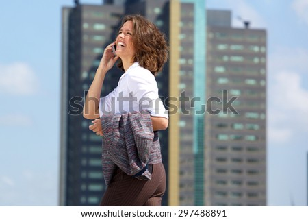 Side portrait of a happy business woman walking and talking on cell phone - stock photo