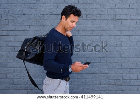 Side portrait of a male traveler walking with cell phone and bag - stock photo