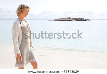 Side portrait of a senior beautiful healthy woman relaxing on a sandy beach shore, smiling on summer holiday, nature outdoors. Travel lifestyle and healthy living, sunny exterior. - stock photo