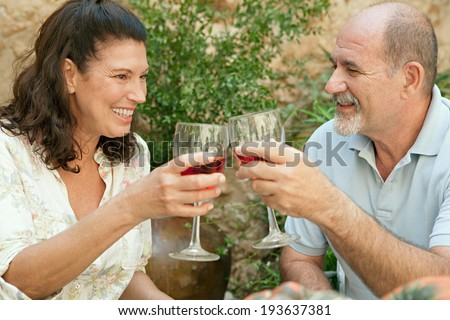 Side portrait of a senior couple relaxing in the garden of a luxury home on holiday, enjoying a glass of wine and toasting. Mature people drinking alcohol sitting at a table. Outdoors lifestyle. - stock photo