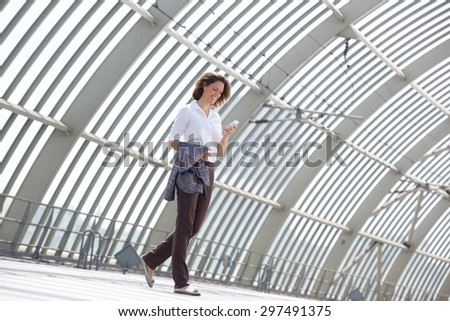 Side portrait of a smiling business woman walking and looking at mobile phone - stock photo