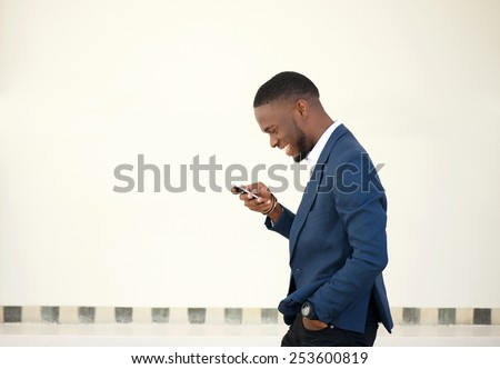 Side portrait of a smiling businessman walking and sending text message on mobile phone - stock photo
