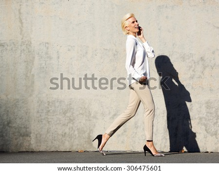 Side portrait of a smiling young attractive woman walking and talking on mobile phone - stock photo