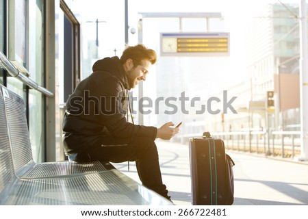 Side portrait of a smiling young man sitting with mobile phone and bag waiting for train - stock photo