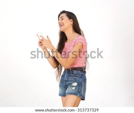 Side portrait of a smiling young woman walking and reading text message on cell phone