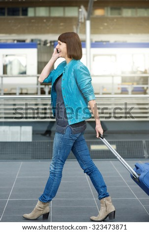 Side portrait of a traveling woman walking with suitcase and mobile phone at airport  - stock photo