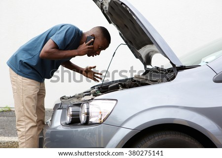 Side portrait of a young african man having trouble with his broken car calling for help on cell phone. - stock photo