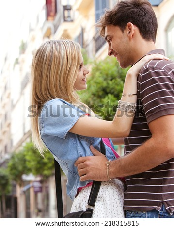Side portrait of a young and attractive couple on holiday, relaxing and embracing while traveling in a destination city shopping street, outdoors. Love, passion and relationships. - stock photo