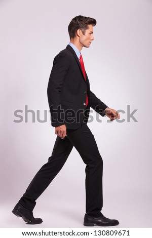 side portrait of a young business man walking on gray background and looking away - stock photo