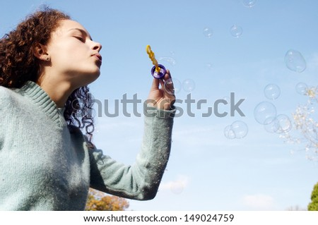 Side portrait of a young girl in a park during the autumn season, wearing a blue jumper and playing at blowing soap bubbles against a blue sky during a sunny winter day.