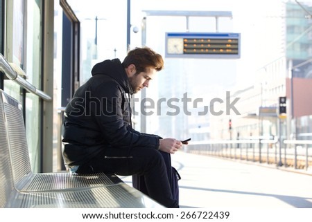 Side portrait of a young man sitting on bench at train station platform with mobile phone - stock photo