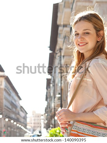 Side portrait of a young teenage girl walking in a city street during a sunny day with large buildings forming a perspective in the background.