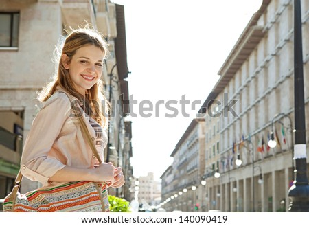 Side portrait of a young teenage girl walking in a city street during a sunny day with large buildings forming a perspective in the background. - stock photo