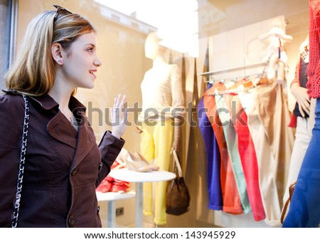 Side portrait of a young teenager girl looking at the clothes in a fashion store shop window, thinking of buying new garments in the city. - stock photo