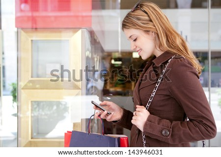 Side portrait of a young teenager tourist visiting the city and carrying paper shopping bags while leaning on a fashion store window, using her smartphone device and smiling. - stock photo