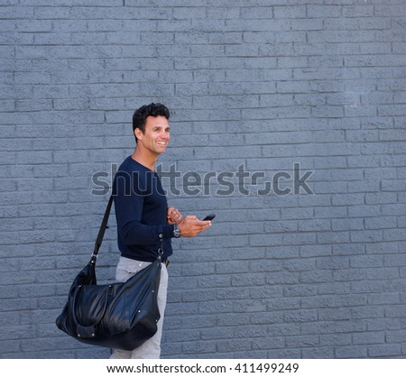 Side portrait of an attractive man walking with mobile phone and bag - stock photo