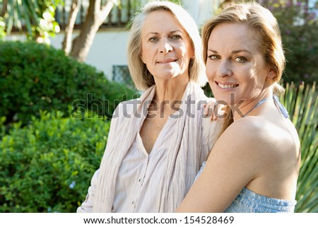 Side portrait of an attractive mature mother and adult daughter spending time together in a home garden during a sunny day, hugging and being proud of each other, outdoors. - stock photo