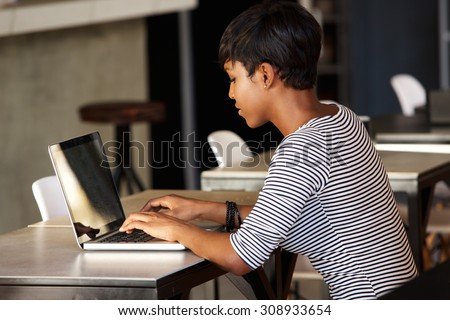 Side portrait of an attractive young african american woman using laptop