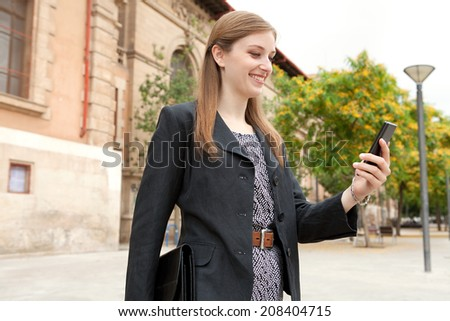 Side portrait of an elegant young professional business woman standing by a grand stone building in the city smiling, holding and using a smartphone. Business people with technology, outdoors. - stock photo