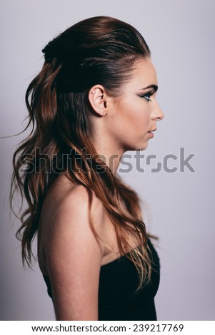 Side portrait of attractive young woman in studio with eyes open - stock photo