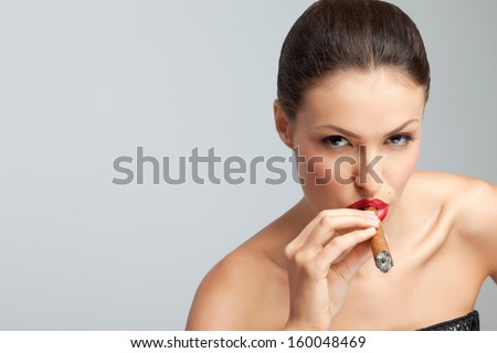 Side portrait of attractive young woman smoking cigar, studio background. - stock photo