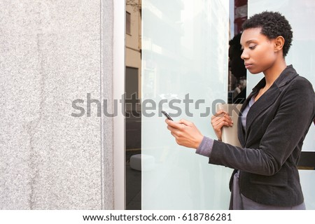 Side portrait of beautiful african american business woman holding smart phone at glass and stone office building, outdoors. Professional black female using technology in city exterior, thoughtful.