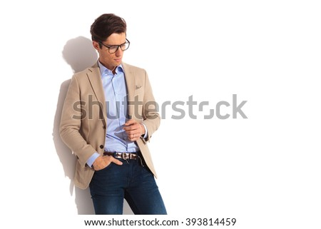 side portrait of businessman wearing glasses with hand in pocket, posing looking down in isolated studio background - stock photo